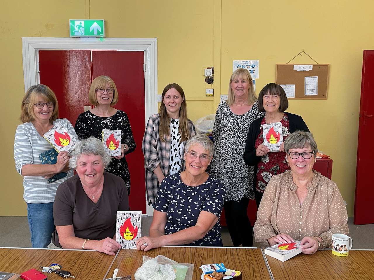 Books & Bakes Book Club members pose with their signed copies of The Disappeared and author Amy Lord at the end of the talk.